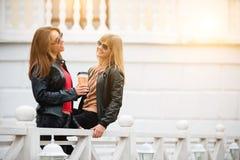 Portrait de deux belles jeunes amies avec les tasses de café de papier dans des mains Photographie stock libre de droits