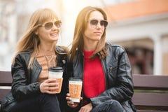 Portrait de deux belles jeunes amies avec les tasses de café de papier dans des mains Images stock