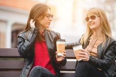 Portrait de deux belles jeunes amies avec les tasses de café de papier dans des mains Photo stock