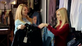 Portrait de deux belles jeunes femmes faisant des emplettes dans une boutique de vêtements banque de vidéos