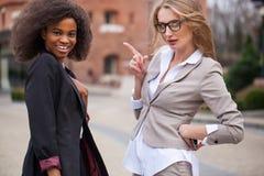 Portrait de deux charmant les femmes d'affaires africaines et caucasiennes souriant et posant pour l'appareil-photo photo stock