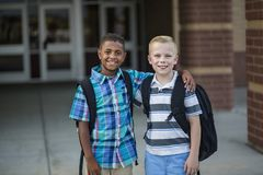 Portrait de deux enfants divers d'école se tenant à l'extérieur de leur bâtiment d'école primaire photo libre de droits
