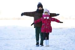 Portrait de deux enfants garçon et fille jouant dehors en hiver Photographie stock