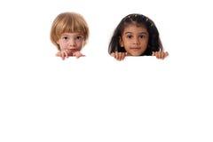 Portrait de deux enfants multiraciaux avec le conseil blanc D'isolement Photo libre de droits
