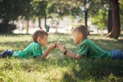 Portrait de deux enfants se trouvant sur l'herbe verte et jouant dans le téléphone portable photos stock