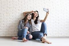 Portrait de deux femelles millénaires, dupant autour devant l'appareil-photo mobile de smartphone Brown a observé les filles modè photos stock