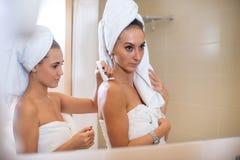 Portrait de deux femmes appliquant la lotion après douche, amis faisant la procédure de soins de la peau Image stock