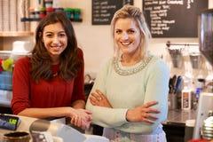 Portrait de deux femmes dirigeant le café ensemble Photographie stock libre de droits