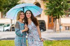 Portrait de deux femmes heureuses avec le parapluie dans la rue Photos libres de droits