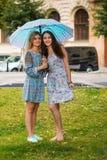 Portrait de deux femmes heureuses avec le parapluie dans la rue Photos stock