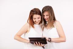 Portrait de deux femmes magnifiques tenant une tablette Photos libres de droits