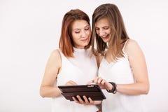 Portrait de deux femmes magnifiques tenant une tablette Photo libre de droits