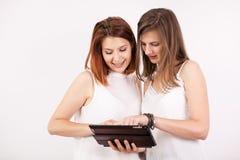 Portrait de deux femmes magnifiques tenant une tablette Photographie stock libre de droits