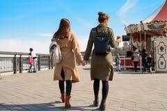 Portrait de deux femmes marchant tenant des mains en parc de ville Photos stock