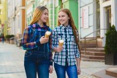 Portrait de deux filles d'adolescent se tenant ensemble mangeantes la crème glacée  Image libre de droits