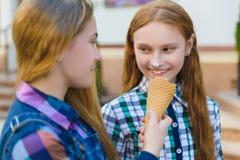 Portrait de deux filles d'adolescent se tenant ensemble mangeantes la crème glacée  Image stock