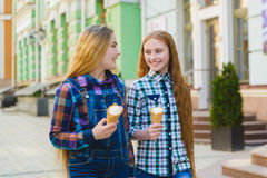 Portrait de deux filles d'adolescent se tenant ensemble mangeantes la crème glacée  Photo libre de droits