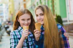 Portrait de deux filles d'adolescent se tenant ensemble mangeantes la crème glacée  Images stock