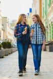 Portrait de deux filles d'adolescent se tenant ensemble mangeantes la crème glacée  Images libres de droits