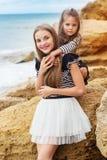 Portrait de deux filles d'amis s'asseyant sur la plage Image libre de droits
