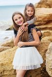 Portrait de deux filles d'amis s'asseyant sur la plage Photo stock
