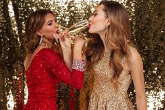 Portrait de deux filles dans des robes brillantes buvant du champagne Photos stock
