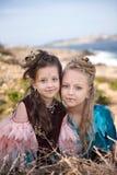 Portrait de deux filles et brunes blondes dans des robes de fantaisie des oiseaux et avec des nids dans les coiffures Images libres de droits