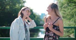 Portrait de deux filles heureuses discutant les dernières actualités de bavardage Image stock