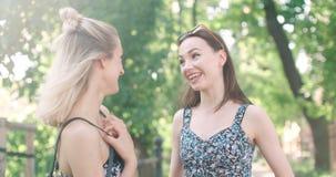 Portrait de deux filles heureuses discutant les dernières actualités de bavardage Photographie stock