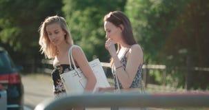 Portrait de deux filles heureuses discutant les dernières actualités de bavardage tout en marchant dans une rue de ville Photo stock