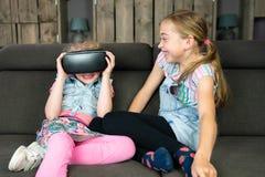 Portrait de deux filles, ils ont l'amusement avec un casque de réalité virtuelle à la maison image libre de droits