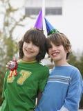 Portrait de deux garçons dans des chapeaux de partie dehors Photographie stock libre de droits