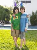 Portrait de deux garçons dans des chapeaux de partie sur la pelouse Photo stock