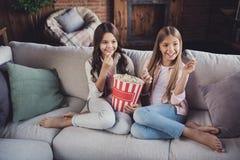 Portrait de deux gentilles belles filles gaies gaies avec du charme fascinantes aimables attirantes douces s'asseyant sur le diva photo stock