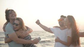 Portrait de deux hommes avec leurs amies étonnantes souriant et étreignant sur le bord de la mer pendant la Windy Weather banque de vidéos