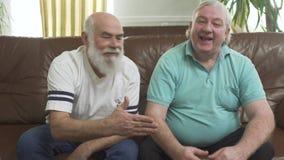 Portrait de deux hommes supérieurs mûrs regardant la TV à la maison Amis observant le football du football tout en mangeant des p banque de vidéos