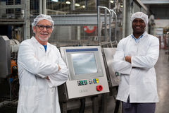 Portrait de deux ingénieurs d'usine se tenant avec des bras croisés Photos stock