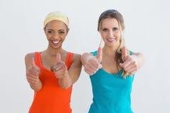 Portrait de deux jeunes amis féminins faisant des gestes des pouces  Photos libres de droits