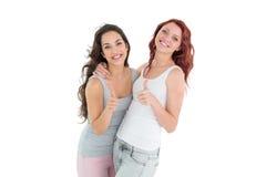 Portrait de deux jeunes amis féminins faisant des gestes des pouces  Photographie stock