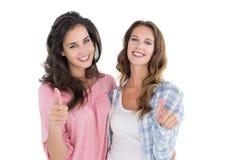 Portrait de deux jeunes amis féminins faisant des gestes des pouces  Image stock