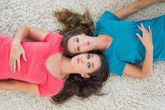 Portrait de deux jeunes amis féminins se trouvant sur la couverture Photos stock