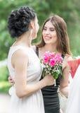Portrait de deux jeunes beaux amis de femmes parlant en parc vert d'été Jolies femelles jeune mariée et étreindre de sourire de d Photo libre de droits