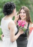 Portrait de deux jeunes belles amies de femmes Jolie jeune mariée avec le bouquet de roses aidant sa demoiselle d'honneur de sour Photos stock