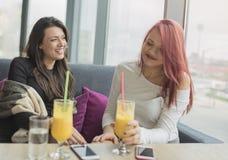 Portrait de deux jeunes belles femmes au café, entretien de fille Images stock