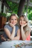 Portrait de deux jeunes belles femmes s'asseyant près d'une table Personnes heureuses Photo stock