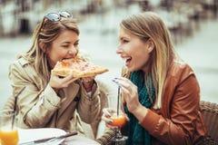 Portrait de deux jeunes femmes mangeant de la pizza Photographie stock libre de droits