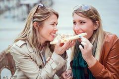 Portrait de deux jeunes femmes mangeant de la pizza dehors Photos libres de droits