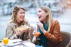 Portrait de deux jeunes femmes mangeant de la pizza dehors Image stock