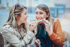 Portrait de deux jeunes femmes mangeant de la pizza dehors Photo libre de droits