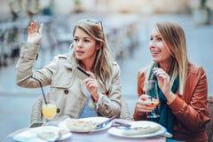 Portrait de deux jeunes femmes mangeant de la pizza dehors Image libre de droits